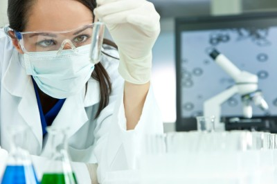 A female medical or scientific researcher or woman doctor looking at a test tube of clear solution in a laboratory with her microscope beside her.