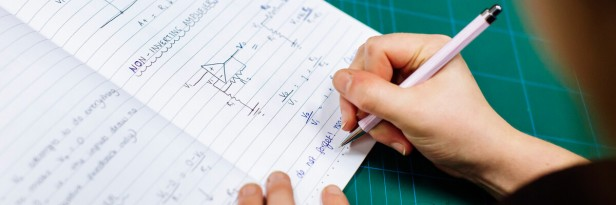 A person writes mathematical equations and electrical forumlae on a notebook.